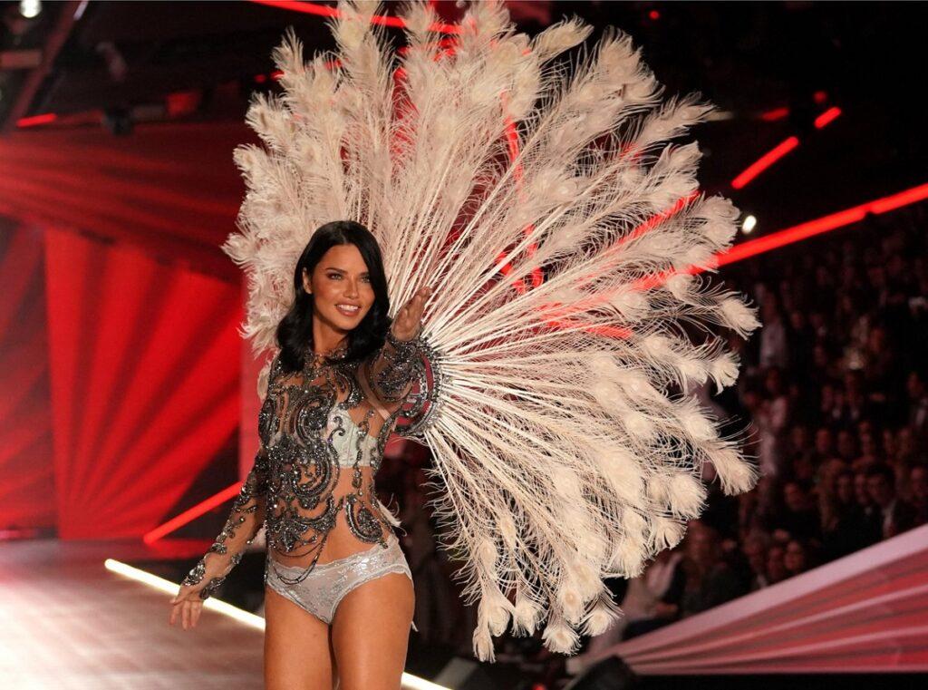 Supermodelul brazilian Adriana Lima în timp ce pozează oe podium și poartă o pereche de aripi albe ample la ultimul său show în anul 2018