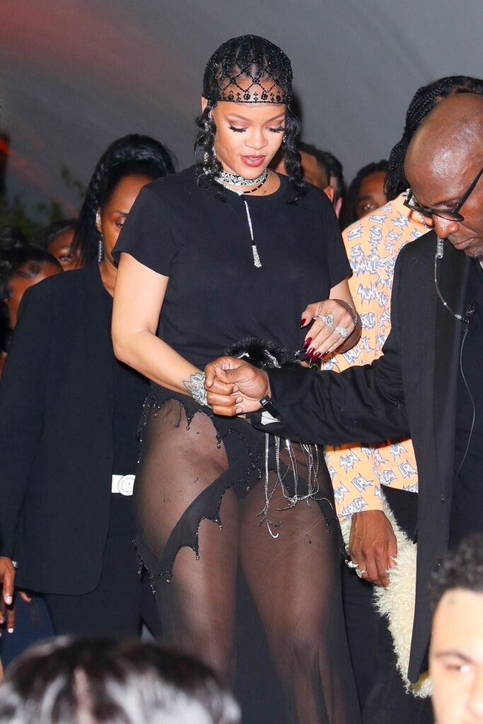 Ținuta Rihannei la petrecerea dată după Met Gala 2021 purtând un tricou negru și o fustă semi transparentă în timp ce este ajutată de un bărbat să coaboare scările