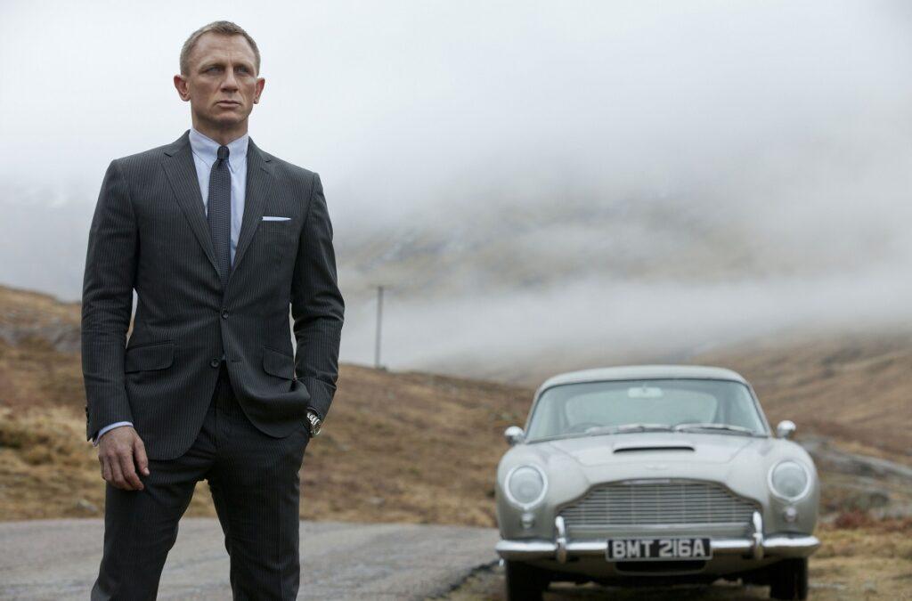 Daniel Craig în filmul Skyfall, lansat în anul 2012. Poartă un costum gri, fundal cu dealurile din Scoția, cu mașina gri în spate