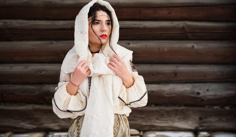 O femeie în costum popular, cu maramă pe cap, machiată superb