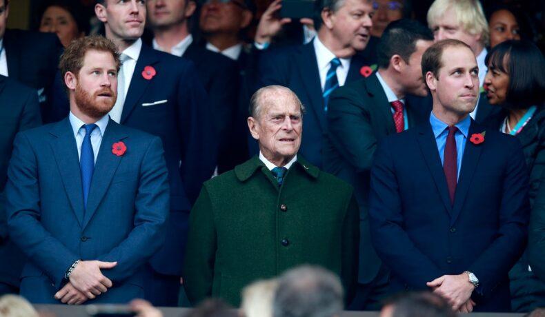 Prințul William, Prințul Harry, Prințul Philip, la finala mondială de rugby, din anul 2015, care s-a ținut în Londra. Philip poartă o haină verde, William și Harry poartă costume închise la culoare