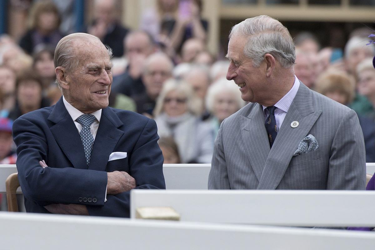 Prințul Philip și Prințul Charles la dezvelirea unei statui a Reginei Elisabeta, în 2016. Cei doi râd și se uită unul la celălalt. Philip poartă un costum albastru închis, Charles poartă un costum gri deschis