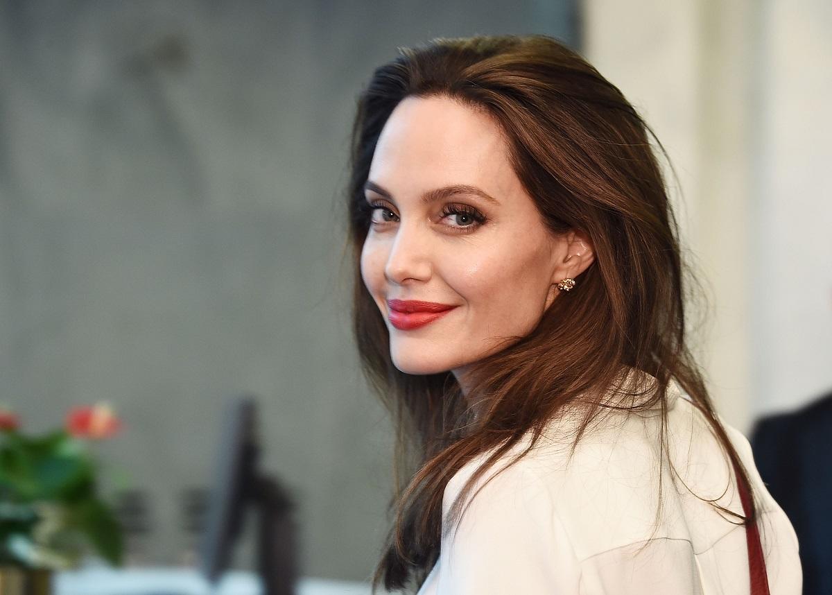 Angelina Jolie la UNited Nations în anul 2017, fotografie portret. E îmbrăcată într=o bluză albă, cu părul închis lung. Zâmbește la cameră și are ruj roșu