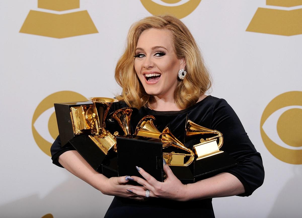 Cântăreața Adele în timp ce ține în mână șase premii muzicale în anul 2012
