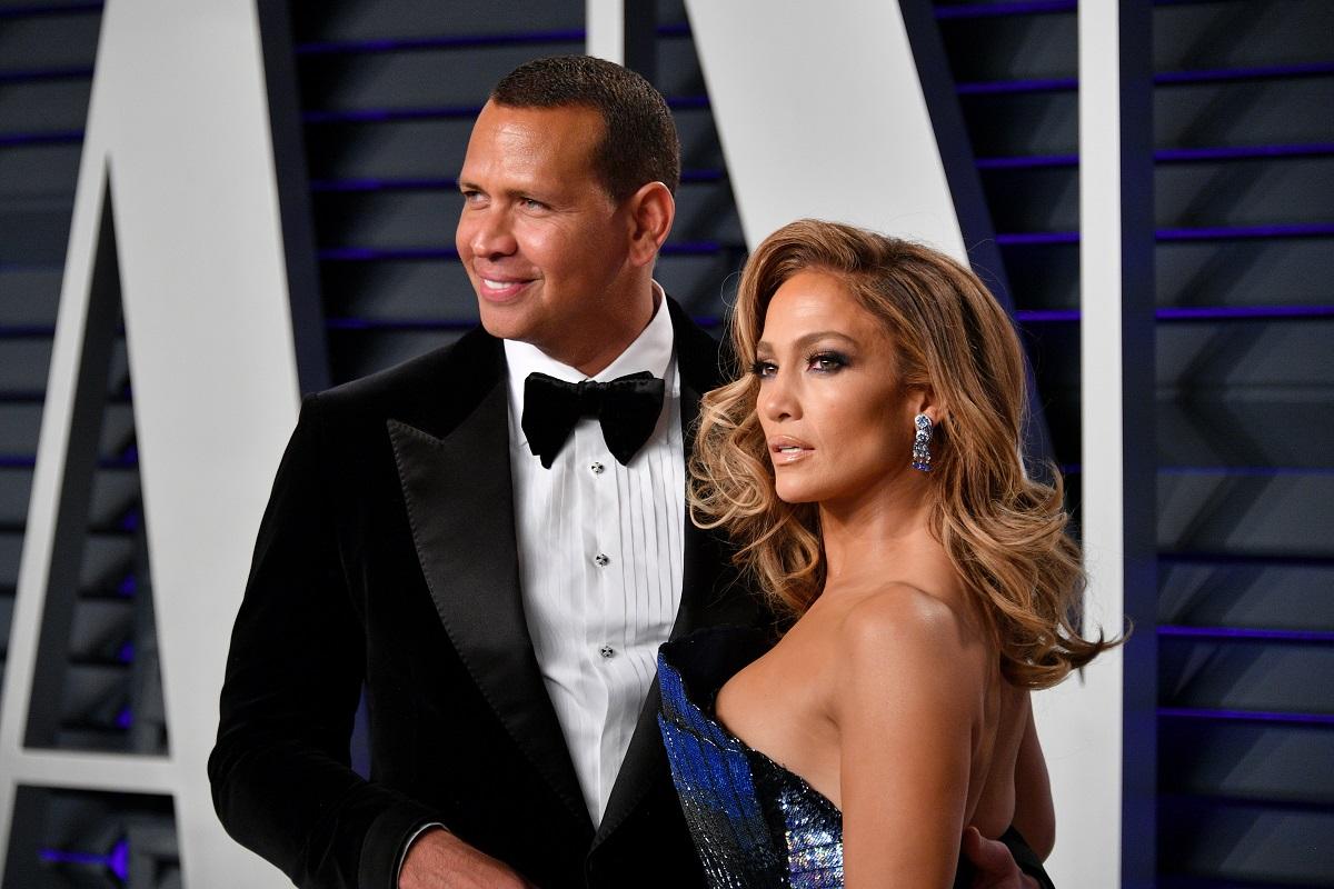 Alex Rogrihuez la costum negru alături de Jennifer Lopez într-o rochie albastră pe covorul roșu la Vanity Fair 2019