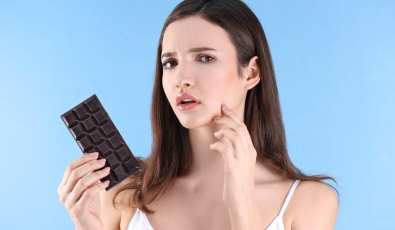 O femeie frumoasă care ține în mână ciocolată, fiind unul dintre acele alimente care cauzează apariția acneei