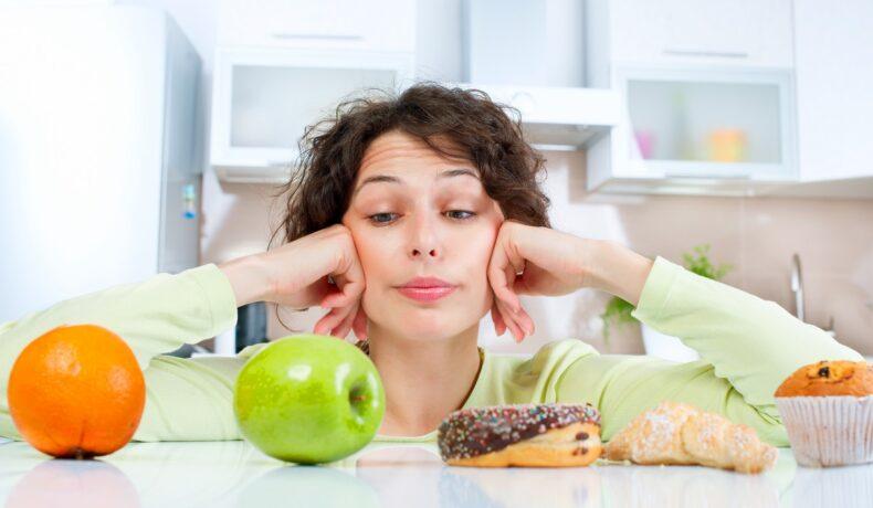 O femeie cu părul creț care stă în fața unui blat în timp ce alege între acele alimente ce care nu ar trebui să le consumi după vârsta de 30 de ani