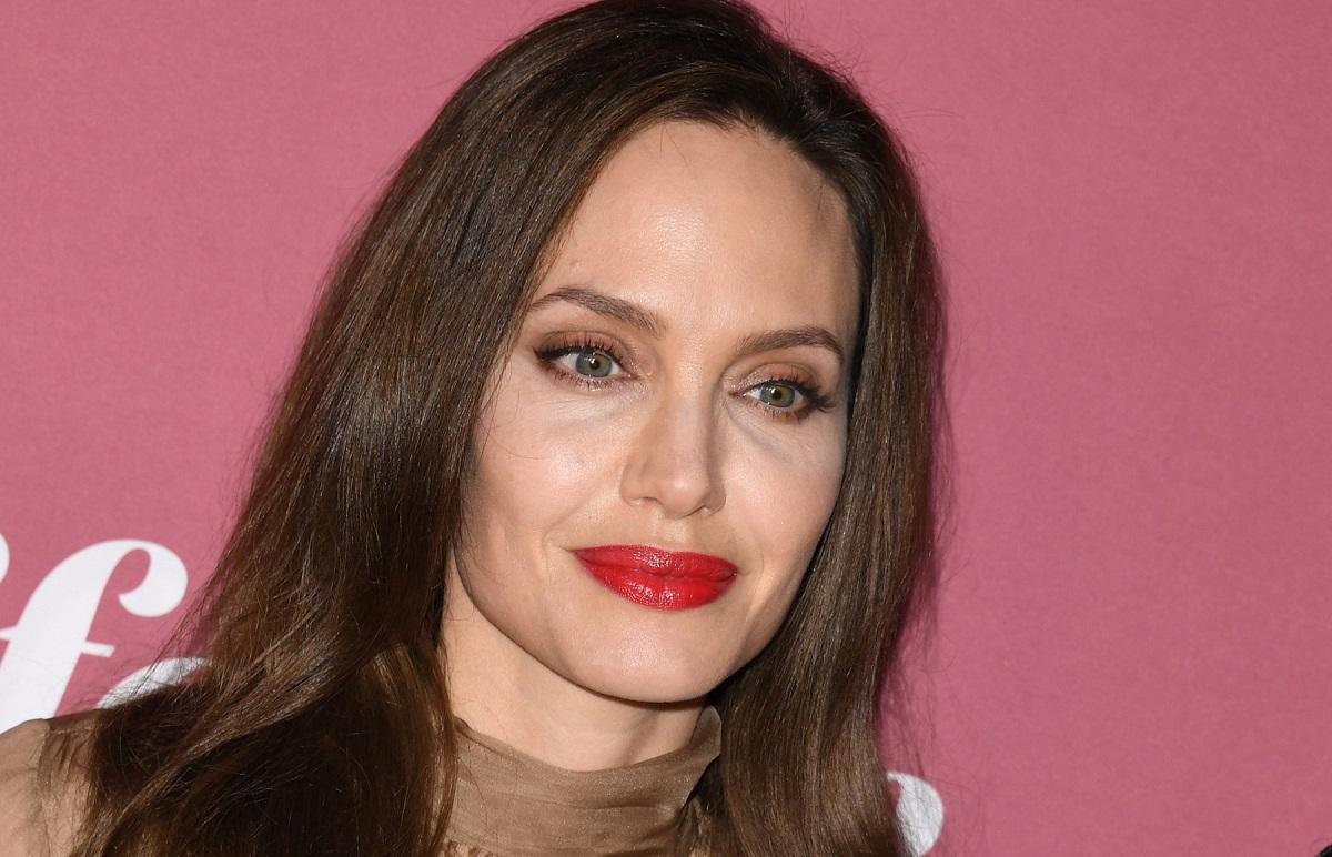Angelina Jolie cu un machiaj natural și ruj roșu în timp ce pozează la un eveniment dedicat femeilor