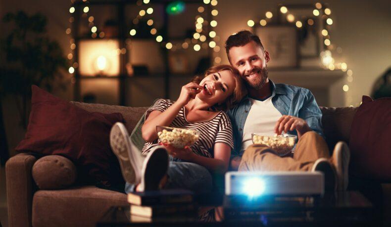 Un cuplu de îndrăgostiți care stau pe canapea și mănâncă floricele în timp ce privesc cele mai bune filme de drgoste din toate timpurile