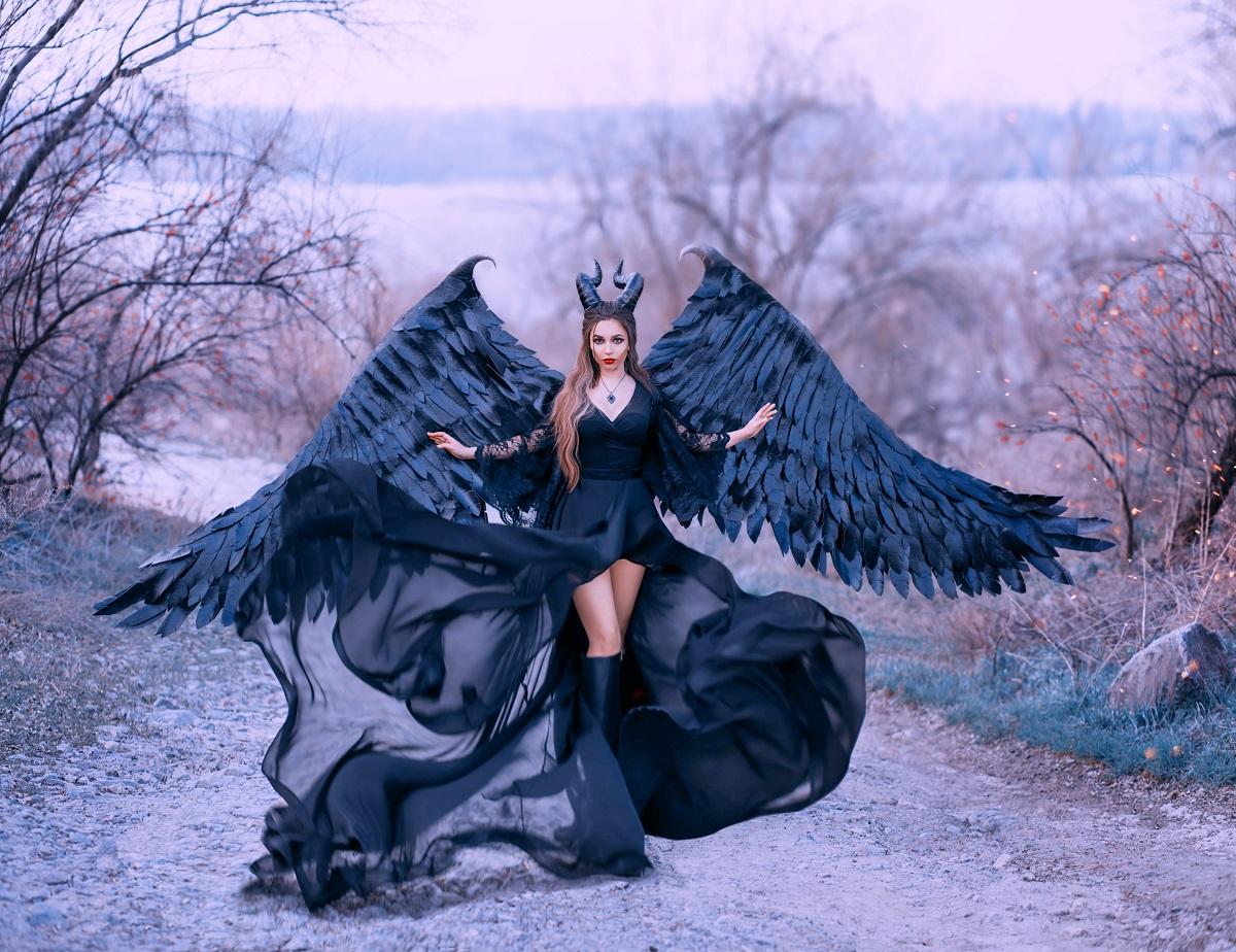 O femeie frumoasă care poartă o rochie neagră și aripi cu pene negre în timp ce înfățișează una din cele mai toxice zodii