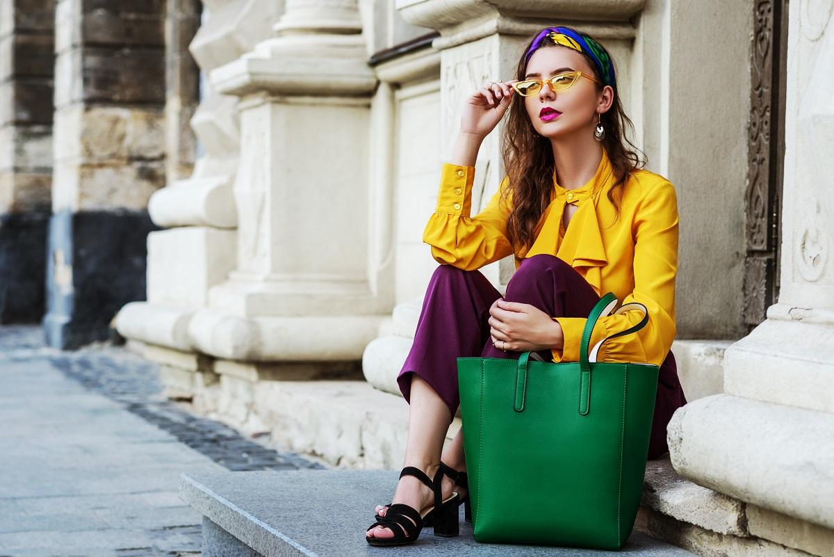 O femeie frumoasă care stă pe niște scări în timp ce paortă culorile sezonului de primăvară-vară 2022, o bluză galbenă, o pereche de pantaloni mov și o poșetă verde