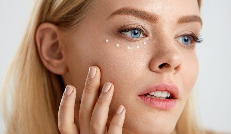 O femeie frumoasă blondă care își aplică cremă hidratantă pe pielea uscată din jurul ochilor