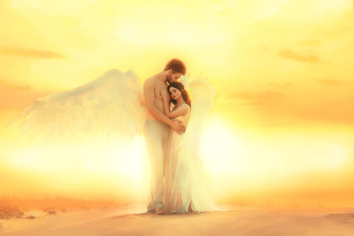 Un cuplu de îndrăgostiți în timp ce se țin în brațe într-un peisaj în care apune soarele