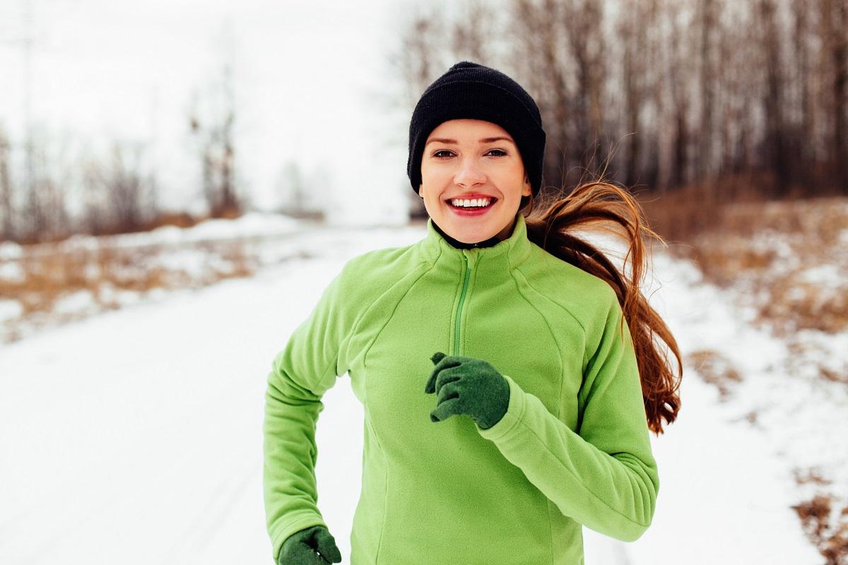 O femeie într-un hanorac verde cu o căciulă neagră pe cap în timp ce aleargă deaorece iarna este cel mai bun moment pentru a pierde în greutate