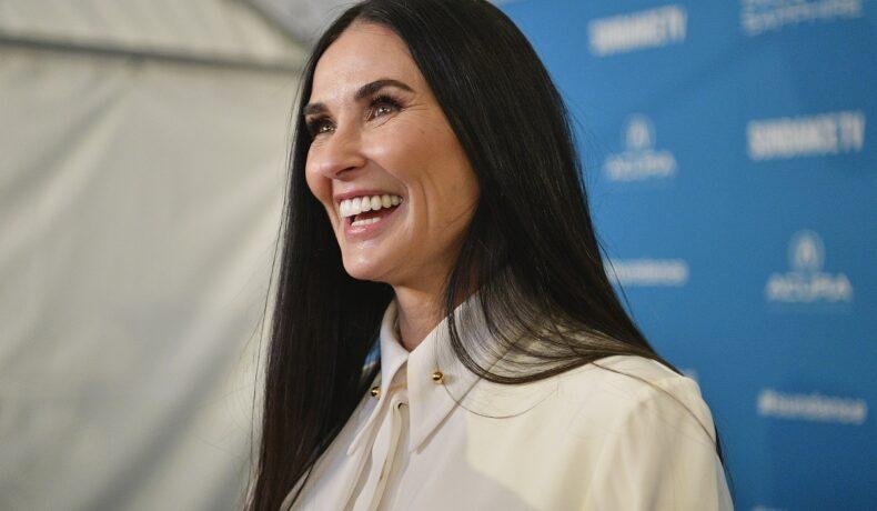 Demi Moore într-o cămașă albă în timp ce zâmbește la un eveniment public