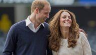 Prințul William într-un hanorac albastru în timp ce o ține după umeri pe Kate Middleton într-un pulover alb