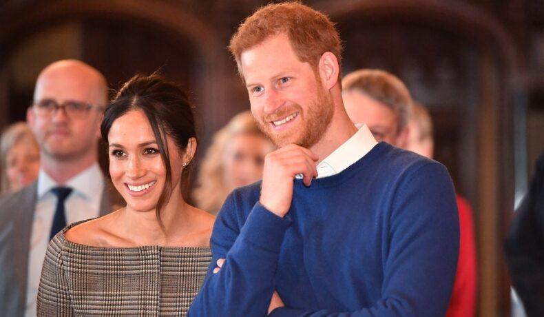 Meghan Markle într-un costum gri alături de Prințul Harry într-un pulover albastru la o ceremonie oficială din Marea Britanie