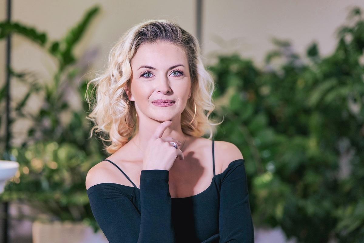 Elwira Petre într-o rochie neagră în timp ce își sprijină fața în mână la interviul pentru CaTine.ro