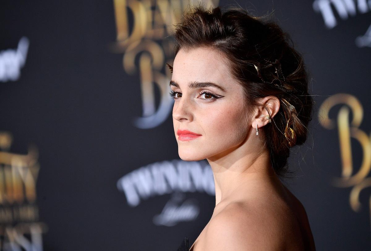 Emma Watson cu părul prins într-un coc în timp ce este pozată pe covorul roșu la premiera filmelor Harry Potter
