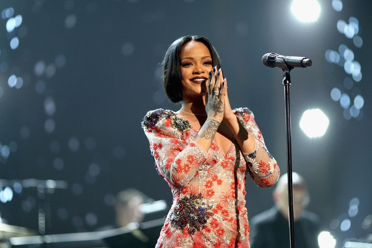 Cântăreața Rihanna într-o ținută de scenă crem cu roșu în timp ce ăși ține mâinile împreunate și zâmbește în fața unui microfon