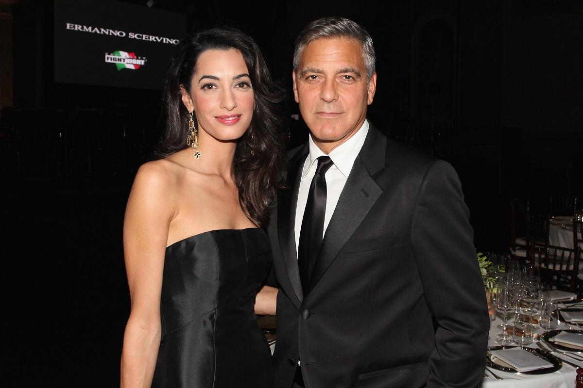 George și Amal Clooney, 2014, la Celebrity Fight Night. Amândoi sunt îmbrăcați în negru. George poartă un costum negru, cu o cămașă albă și o cravată neagră. Amal poartă o rochie neagră fără bretele
