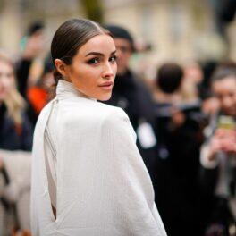 Olivia Culpo, la Săptămâna Modei de la Paris, în anul 2018, la spectacolul Nina Ricci. Poartă o bluză albă, lungă, paparazzi în spate, fără greșeală vestimentară