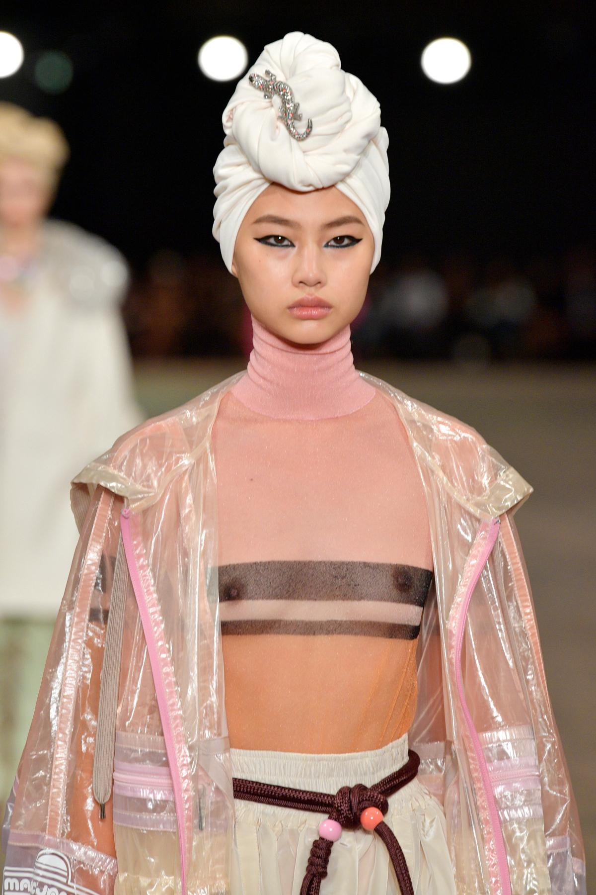 Hoyeon Jung, cu turban alb pe cap și îmbrăcată într-o ținută în nuanțe roz pudră, defilează la prezentarea casei de modă Marc Jacobs, în anul 2018.