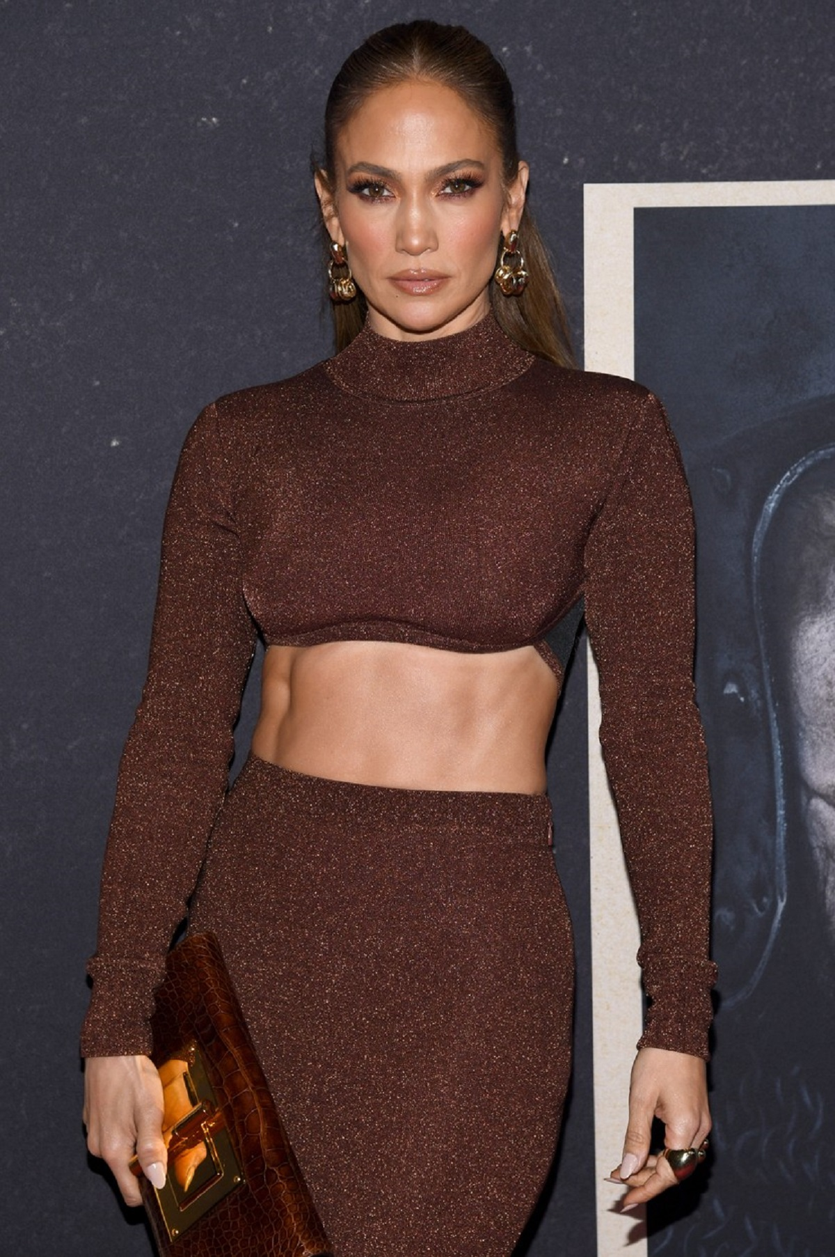 Jennifer Lopez într-o costumație maro cu o fustă scurtă și un crop top pe covorul roșu la premiera filmului The Last Duel