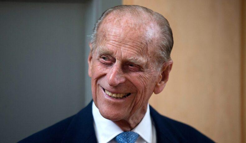 Prințul Philip, în anul 2015, într-o vizită la Richmond Adult Community College. A purtat un costum negru, o cămașă albă și o cravată albastră