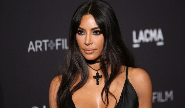 Kim Kardashian într-o rochie neagră cu un lănțisor negru la gât în timp ce pozează pe covorul roșu