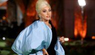 Lady Gaga într-o rochie neagră cu o eșarfă albastră în timp ce pozează pe covorul roșu în Las Vegas