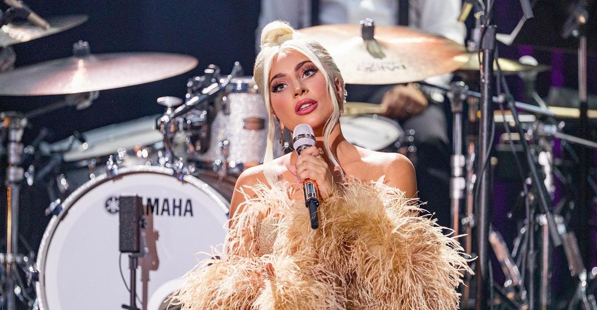 Lady Gaga într-o rochie aurie cu blană în timp ce se află pe scenă și cântă, după ce a s-a fotografiat fără machiaj