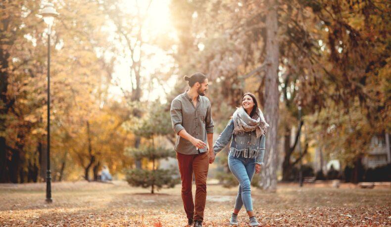 Un cuplu de îndrăgostiți care se țin de mână și se plimbă într-un parc din București toamna