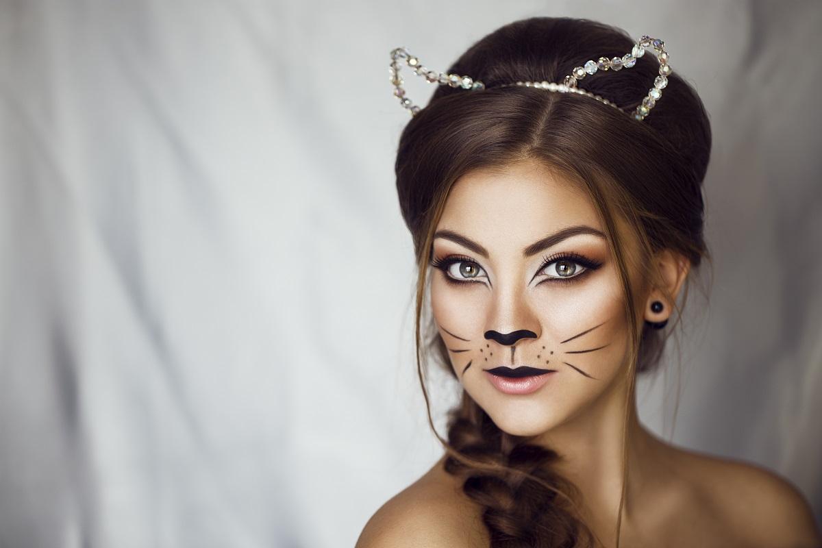 O femeie frumoasă cu un look de felină după ce a aplicat unul din acele machiaje de Halloween