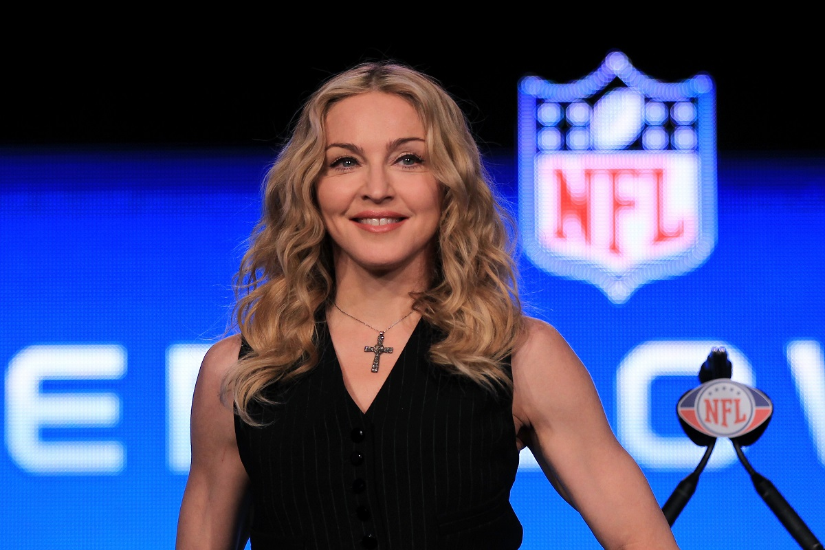 Madonna într-o bluză neagră pe scenă în fața unui microfon