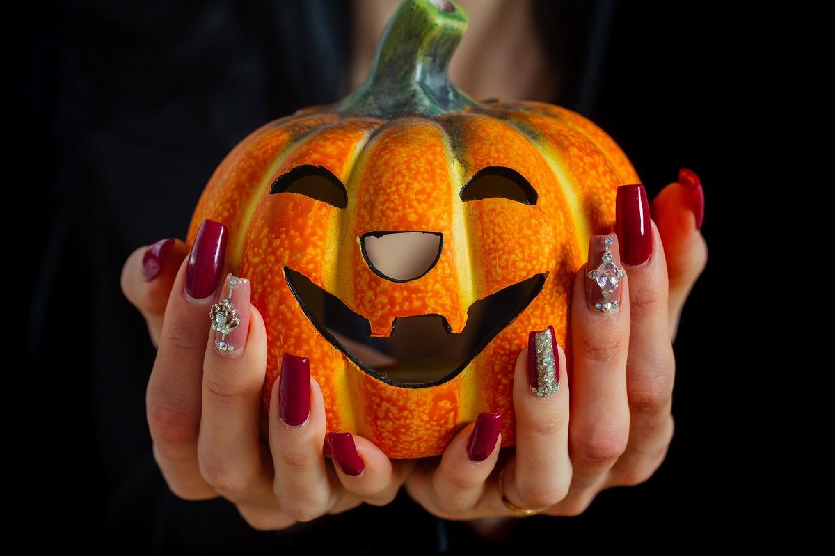 Un dovleac portocaliu cu o față zâmbitoare în timp ce este ținut în aer de două mâini cu modele de unghii pentru Halloween