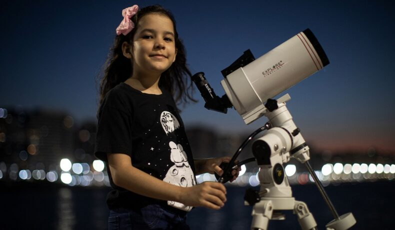 Nicole Oliveira e cea mai tânără astronomă din lume, la doar 8 ani. Ea colaborează cu un proiect NASA. În imagine poartă un tricou negru, o fundă roz, și se uită printr-un telescop alb