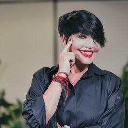 Concurenta de la Asia Express, Patrizia Paglieri, cu mâna pe față în timp ce zâmbește la cameră pentru interviul echipei CaTine.ro
