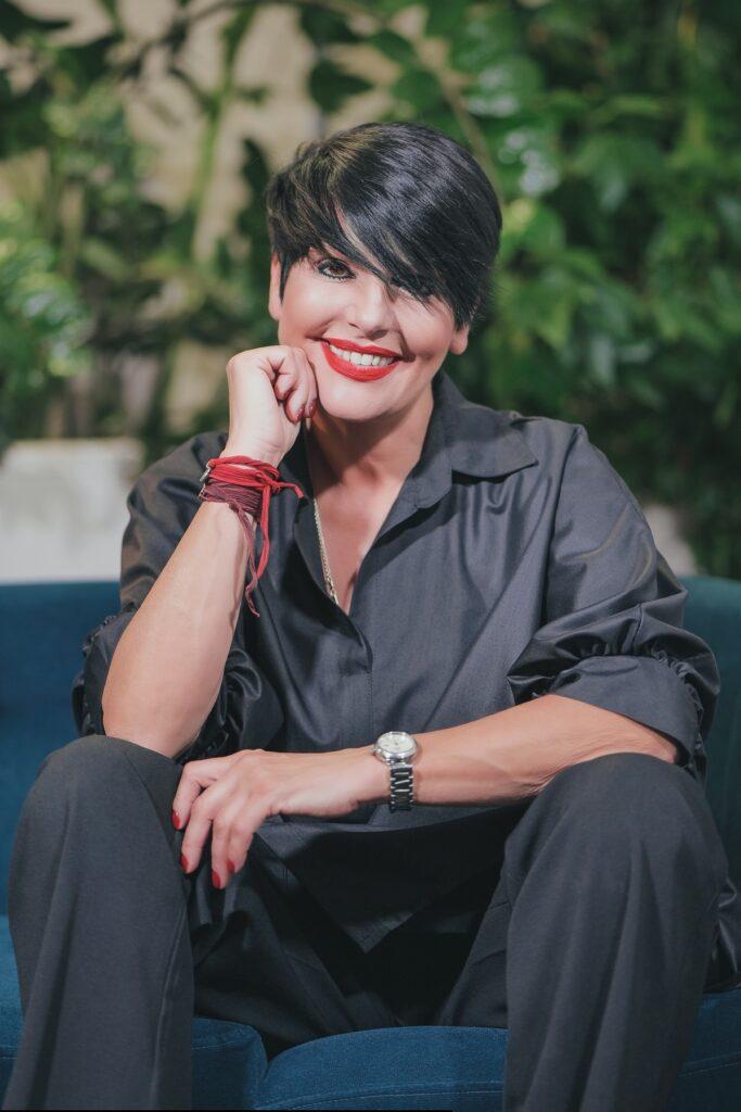Concurenta Patrizia Paglieri în timp ce stă cu fața sprijinită într-o mână și zâmbește în cadrul interviului CaTine.ro despre experiența de la Asia Express: Drumul Împăraților