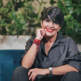 Patrizia Paglieri cu mâna sub bărbie într-o cămașă neagră, stând pe o canapea albastră la interviul CaTine. ro despre experineța Asia Express