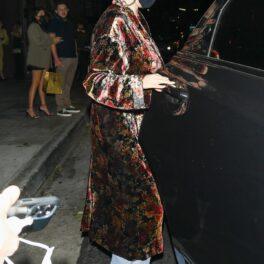 Selena Gomez care a purtat un palton cu imprimeu floral și o pereche de blugi mom fit în timp ce urcă într-o mașină neagră