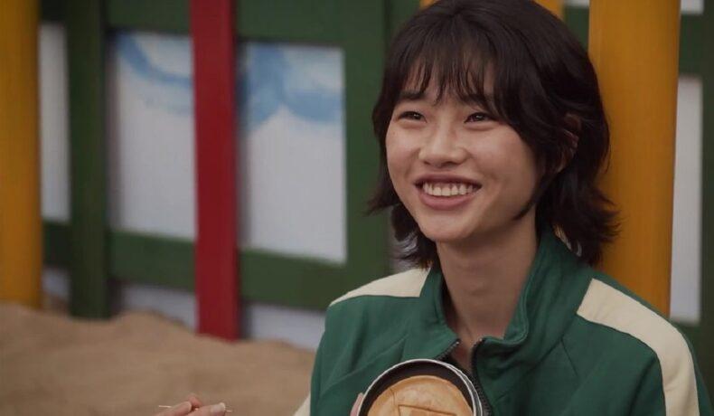 Jucătoarea numprul 067 în timp ce zâmbește și realizează unul din jocurile din serialul Squid Game care ar putea fi nominalizat la Premiile Emmy 2022
