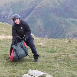 Tom Cruise alături de echipa de filmare pe un munte în timp ce își pregătește parașuta