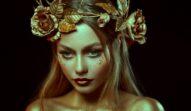 O femeie frumoasă care este acoperită de o vopsea aurie și poartă o coroniță cu flori și frunze în timp ce reprezintă una din cele trei zodii ghinioniste în ziua de 26 otcombrie 2021