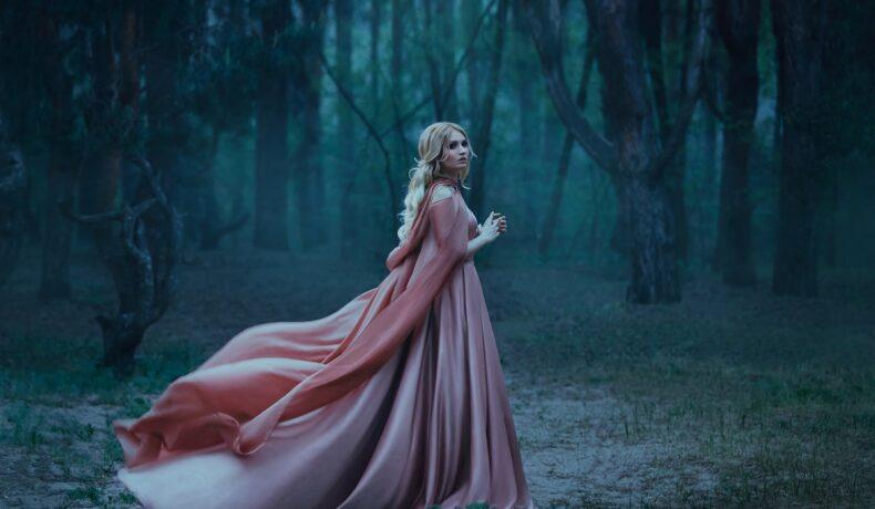O femeie frumoasă care poartă o rochie roz într-o pădure întucenactă în timp ce întruchipează una din acele zodii ghinioniste în ziua de 7 octombrie 2021
