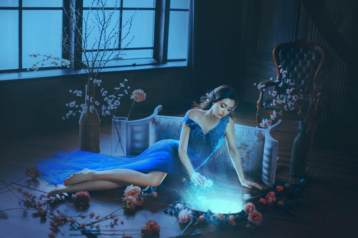 O femeie frumoasă care stă întinsă pe podea într-o rochie albastră în timp ce privește în oglindă