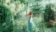 O femeie frumoasă care poartă o rochie albastră în timp ce se află într-o grădină cu multă verdeață și cu trandafiri roși și privește în față, reprezentând una din cele trei zodii norocoase în ziua de 23 octombrie 2021