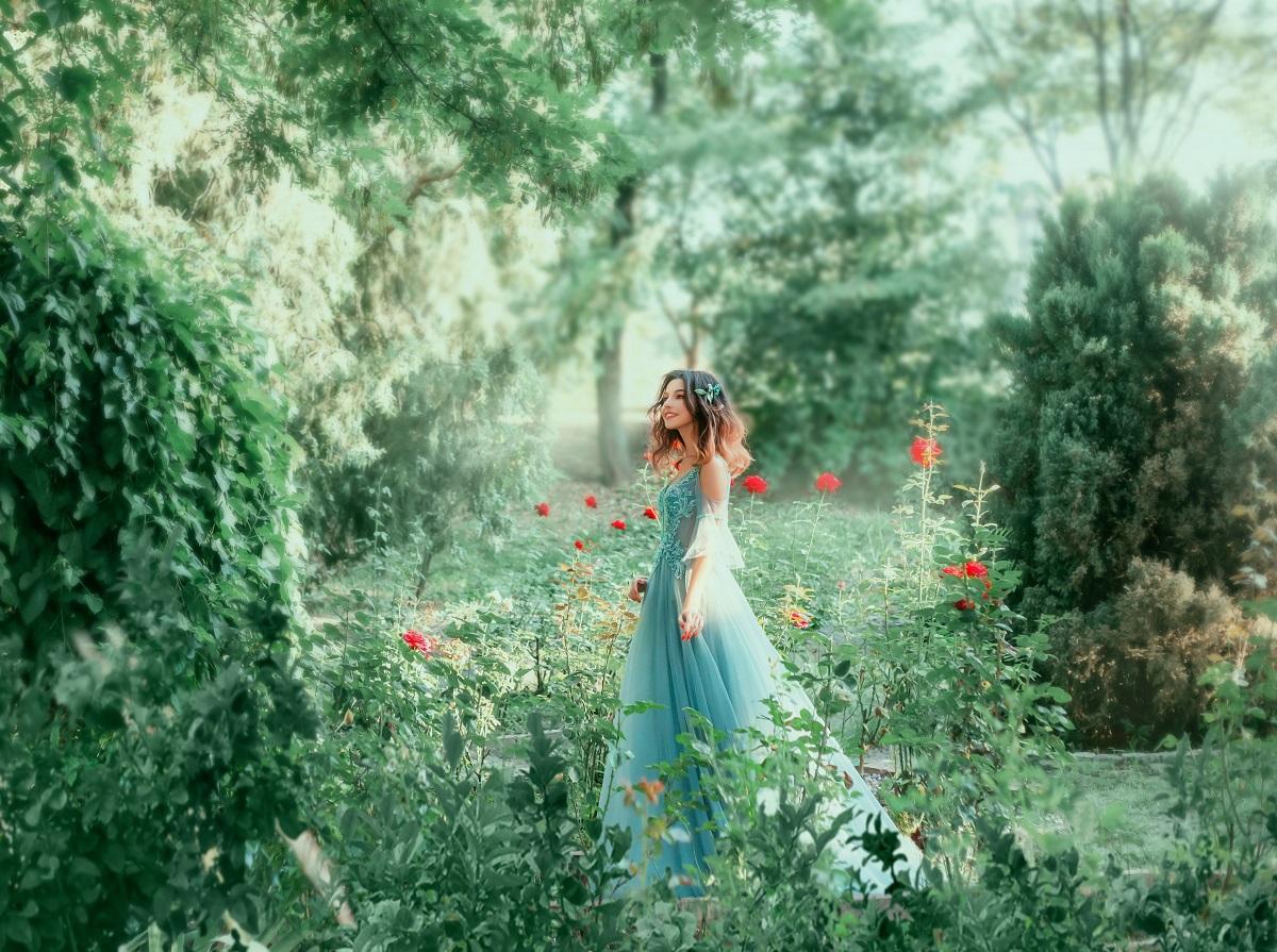 o femeie frumoasă care poartă o rochie albastră și stă în pădure pe un câmp înconjurat cu flori în timp ce este una dintre cele trei zodii norocoase în ziua de 5 octombrie 2021