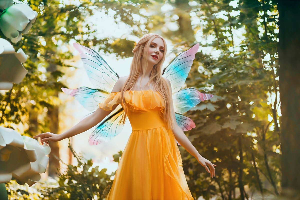 O femeie frumoasă blondă care poartă o rochie galbenă și are în spate ariăi de zână pentru a reprezenta una din cele trei zodii norocoase în ziua de 9 octombrie 2021