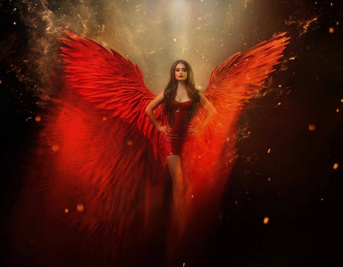 O femeie frumoasă care poartă o rochie roșie și are în spate aripi de înger roșii în timp ce reprezintă una din acele zodii periculoase